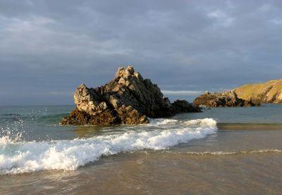 Waves strike a beach in Scotland's Northern Highlands