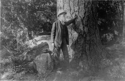 John Muir standing by a tree