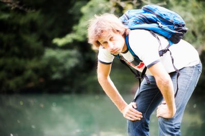 Male hiker resting his hands on knees, exhausted