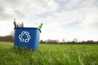 A blue recycling bin sitting in a field