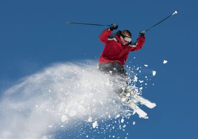 Young man in mid-air making ski jump.