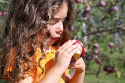 Girl_eating_apple_in_orchard_istock